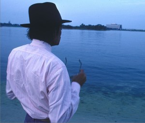 MJ looking out on the river with hat on and glasses in hand